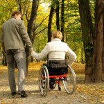 Husband and handicapped wife taking stroll in park alley in fall time