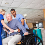 Healthcare workers helping patient into wheelchair